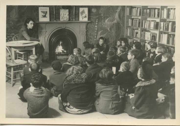 Circa 1940s Boys and Girls House storytime.  Children's librarian reading to a group.