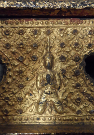 Detail from the wooden case above, showing a guardian figure or deva on a flowery background made from metal wire, lacquer and very thin gold leaf. The metal wire circles used to be decorated with mirror glass inlay which has been lost. British Library Or.16820/B