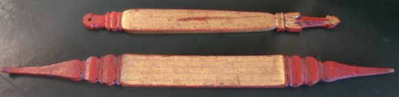 Two wooden title indicators covered with red lacquer, with text incised in Tham script on a gold background. Lanna, 19th century. British Library, Or.14528-9.