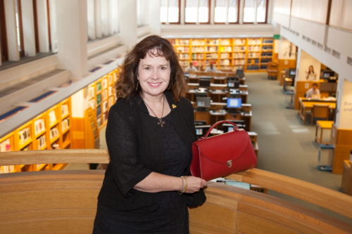 Image of Julie Deane in The British Library displaying a red handbag