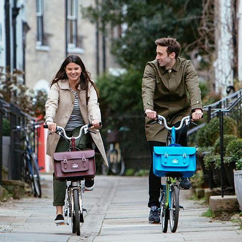 Image of a man and woman riding Brompton Bikes with The Cambridge Satchel attached to the front