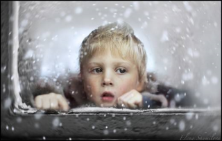 Child-looking-through-window-in-snow