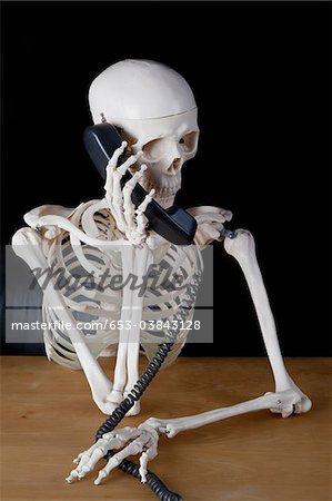 653-03843128em-A-skeleton-using-a-landline-phone