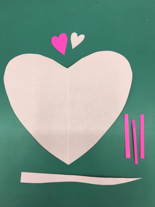 Three pink paper hearts (two small and one large), three small dark pink strips of paper, and one long light pink strip of paper.