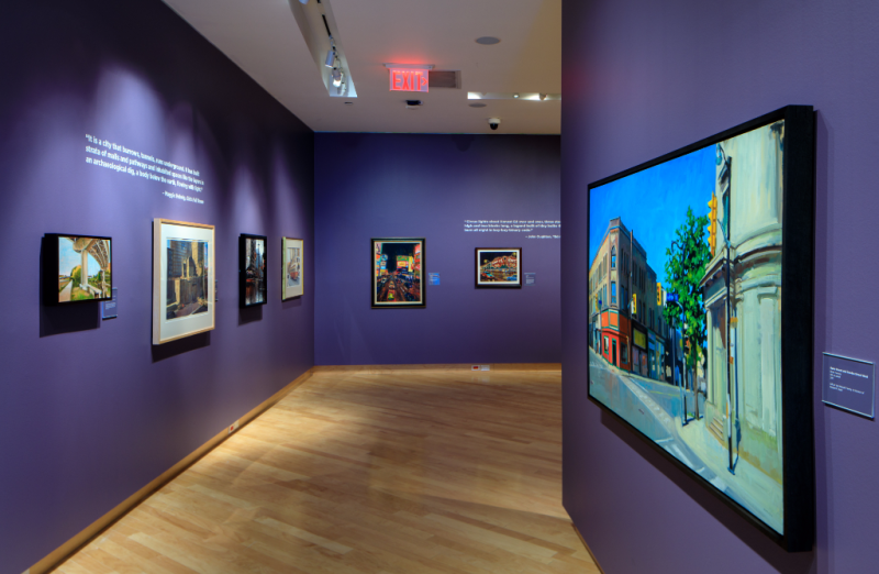 Inside the TD Gallery with paintings hanging on purple walls