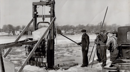 Men with poles use deviceto break up ice on froze river