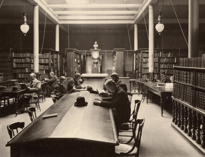 Men in old library reading with hats placed on tables